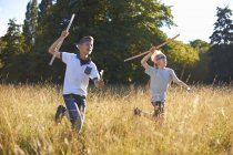 Два маленьких мальчика бегут с луками и стрелами — стоковое фото