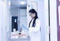 Femme scientifique préparant l'équipement d'expérience pour chariot en laboratoire — Photo de stock