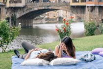 Lesbian couple lying on blanket in front of Ponte Vecchio over river Arno, Florence, Tuscany, Italy — Stock Photo