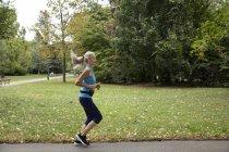 Mature female runner running in park — Stock Photo