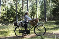 Mature woman cyclist with foraging baskets on forest path — Stock Photo