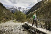Giovane donna escursionismo sulla passerella, Holzgau, Tirolo, Austria — Foto stock