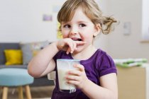 Fille tenant verre de lait à la maison — Photo de stock