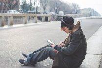 Человек с помощью цифрового планшета на бордюр, Милан, Италия — стоковое фото