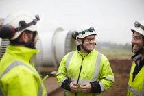 Инженеры беседуют на площадке строительства ветряных электростанций — стоковое фото