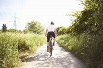 Vista trasera del atleta masculino ciclismo en camino rural - foto de stock