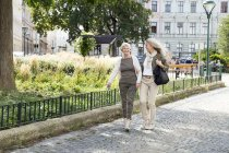 Mother and daughter walking along street together — Stock Photo