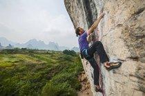 Mâle grimpeur escalade au Mont blanc - une falaise de calcaire à Yangshuo, Guangxi Zhuang, Chine — Photo de stock