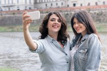 Lesbian couple using smartphone to take selfie next to Arno river, Florence, Tuscany, Italy — Stock Photo