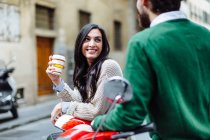Young couple leaning on moped with takeaway coffee, Florence, Italy — Stock Photo