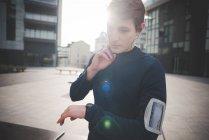 Молодой бегун проверяет пульс шеи на городской площади — стоковое фото