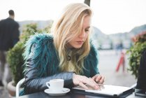 Young woman using digital tablet at sidewalk cafe — Stock Photo