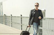 Mature man pulling wheeled suitcase — Stock Photo