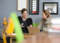 Female printer and designer using laptop in workshop office — Stock Photo