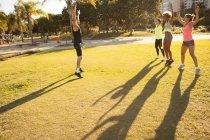 Três mulheres novas que exercitam com o instrutor no parque — Fotografia de Stock