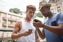 Deux hommes regardant les smartphones — Photo de stock