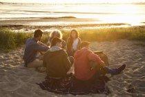 Молоді друзі picnicing на заході сонця на Борнмут Біч, Дорсет, Великобританія — стокове фото
