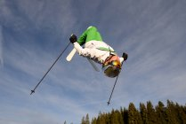 Man backflipping upside down mid air whilst freestyle ski jumping — Stock Photo