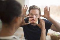 Mujer sosteniendo teléfono inteligente en frente de la boca del hombre - foto de stock
