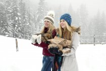 Two young female friends carrying logs in snowy mist — Stock Photo