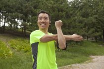 Молоді чоловіки бігун розтягування зброї в парку — стокове фото