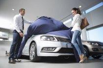 Venditore alla scoperta di auto nuove per il cliente femminile in concessionaria auto — Foto stock