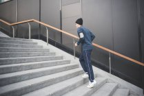 Young male runner moving up city stairs — Stock Photo