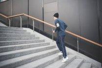 Jeune mâle coureur gravir les escaliers de la ville — Photo de stock