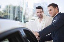 Cliente masculino e vendedor conversando na concessionária de carros — Fotografia de Stock