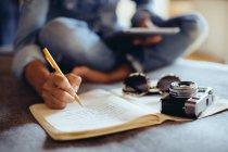 Recadrée tir du milieu femme adulte assis sur le lit dans cahier d'écriture — Photo de stock