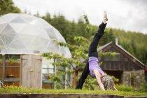 Літні жінки, які практикують йогу ногою, підняті в саду eco lodge — стокове фото