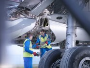 Engineers recycling aircraft parts from airplane on runway — Stock Photo