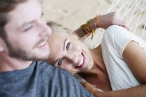 Close up of smiling young couple on beach hammock — Stock Photo