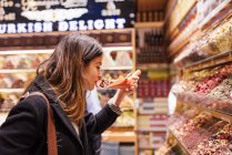 Young woman smelling food in market, Istanbul, Turkey — Stock Photo