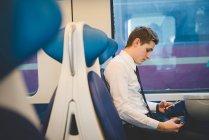 Портрет молодой бизнесмен пригородных, используя цифровой планшет на поезде. — стоковое фото