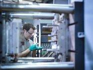 Рабочий осмотр деталей формовочной машины пластмасс — стоковое фото