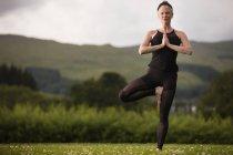 Літні жінки, які практикують йогу дерево позиції в галузі — стокове фото