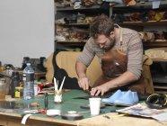 Shoemaker working in workshop, selective focus — Stock Photo