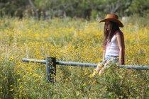 Sullen дівчина в ковбойському капелюсі сидячи на паркан у полі — стокове фото
