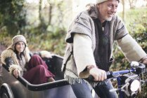 Mature hippy couple riding tricycle and trailer on rural road — Stock Photo