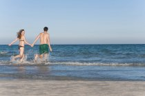 Couple walking in sea together — Stock Photo
