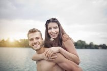 Young man giving his girlfriend a piggyback in lake — Stock Photo