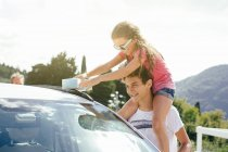 Brother and sister washing car outdoors — Stock Photo