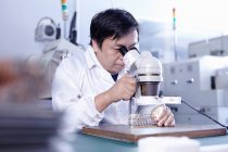 Technician using microscope in LED factory in Guangdong, China — Stock Photo