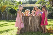 Five girls pouring lemonade and chatting at lemonade stand in park — Stock Photo