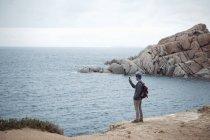 Junger mann steht auf klippe mit dem smartphone zu fotografieren meer, costa smeralda, sardinien, italien — Stockfoto