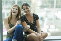 Cheerful young women sitting together and laughing — Stock Photo