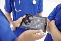 Médecins qui regardent des scans sur tablette numérique — Photo de stock