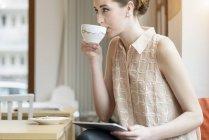 Junge geschäftsfrau im Café Kaffee trinken und mit digital-Tablette — Stockfoto