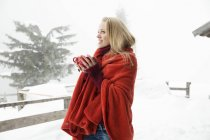 Young woman in snowy mist wrapped in red blanket drinking coffee — Stock Photo